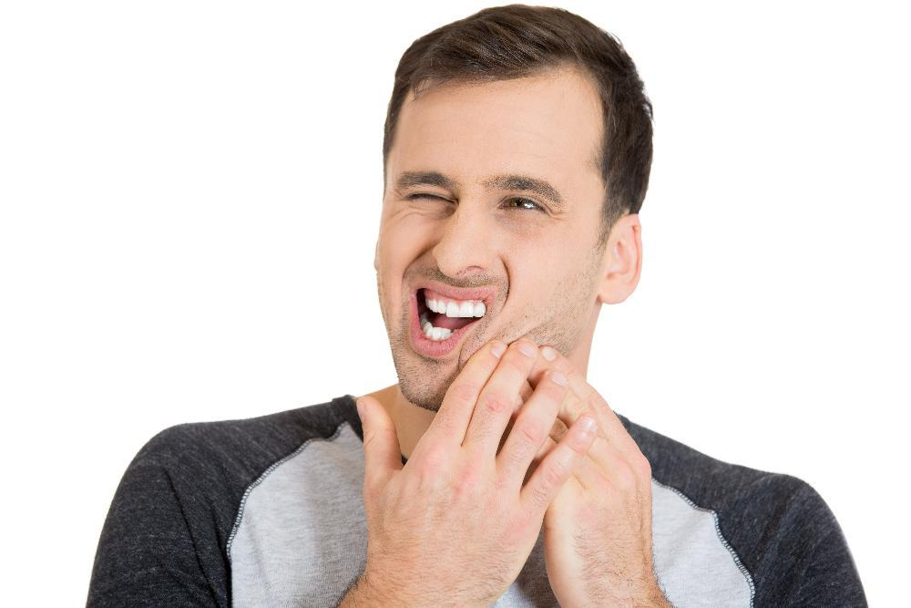 Man with bad tooth pain from a Dental Emergency near Greeley CO