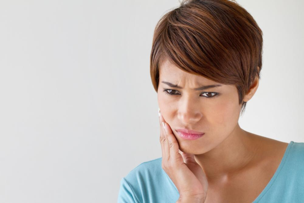Woman holding jaw in pain | Dentist Greeley CO