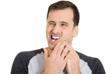 man holding jaw from pain | Dentist Greeley CO