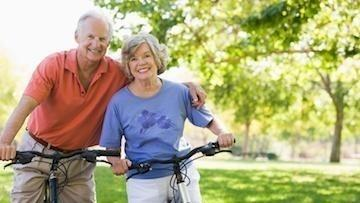 Older couple biking in park | Dentist Greeley CO